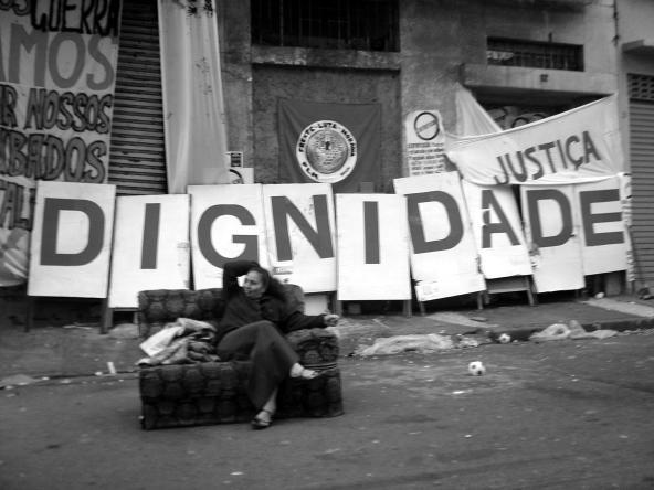 Uma mulher na rua pedindo por justiça e dignidade.